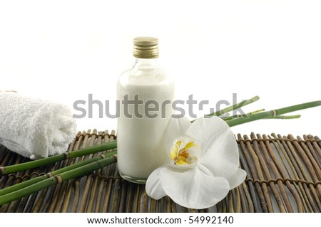 towel and orchid with massage oils on mat - stock photo