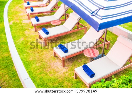 Towel and pillow on bed pool around swimming pool in hotel resort - Vintage Light Filter - stock photo