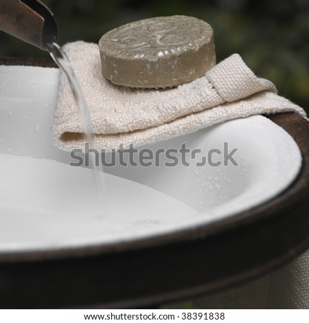 Towel and soap in the wash basin - stock photo