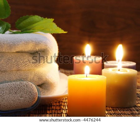 Towel, aromatic candles and other spa objects to make mood relaxing - stock photo