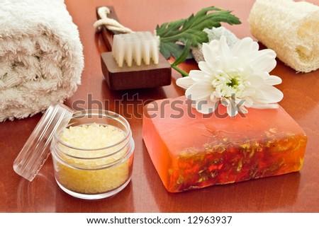 towel brush loofah sea-salt soap and flower arrangement - stock photo