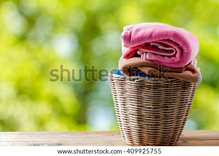 Towel in a laundry basket on natural background - stock photo
