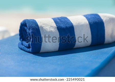 towel on a sun lounger on the beach. - stock photo