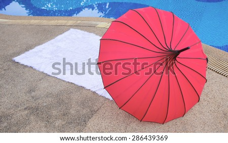Towel  red umbrella on the empty sunbed by the resort pool - stock photo