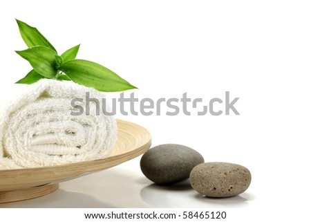 Towel with bamboo leaf and pebbles  over white - stock photo