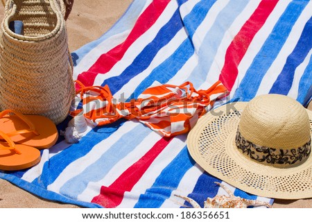 towel with swimming assesories  at sunny day on sandy beach
