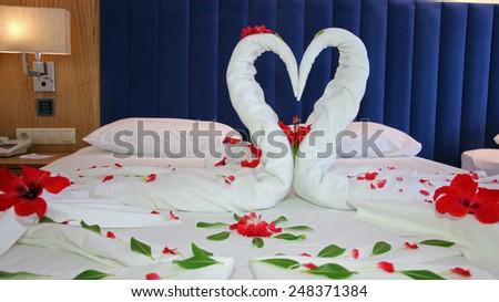 Towels Arranged As Swans On The Bed In Hotel Room Romantic Flower Petal Arrangement