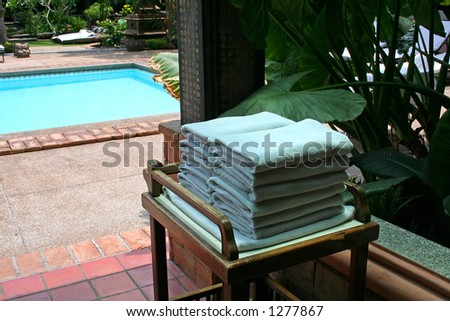 Towels next to the pool in a tropical resort