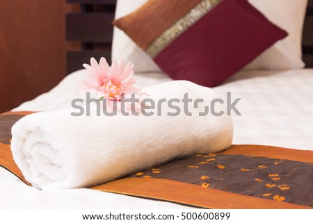 Towels placed on the bed. With pink flowers lay nearby.