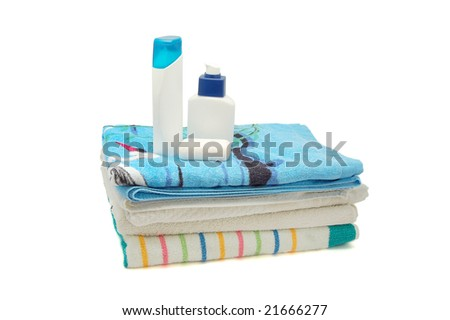 Towels, shampoo and soap on white