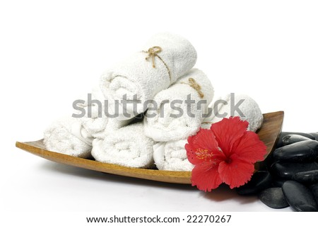Towels stacked in wood bowl with flower, stone - stock photo