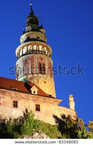 Tower at Cesky Krumlov's Castle.  The tower is decorated with paintings and patterns.  It's an historic sight in a tourist town. - stock photo