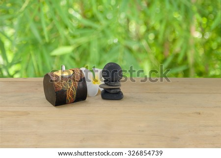 tower black stone and candle on the wooden table - stock photo