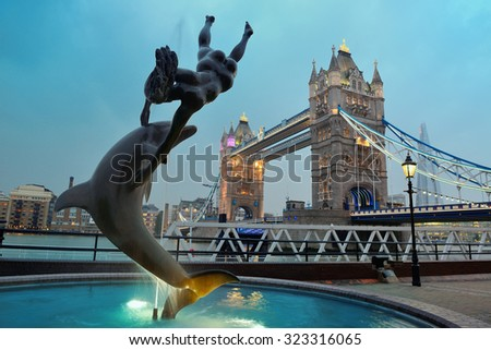 Tower Bridge and statue of a girl playing with dolphin in St Katharine docks in London. - stock photo
