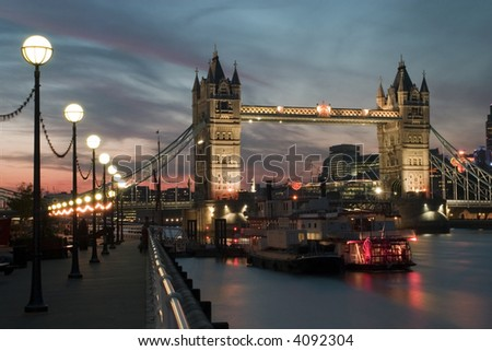 Tower Bridge at night in in London with boats.