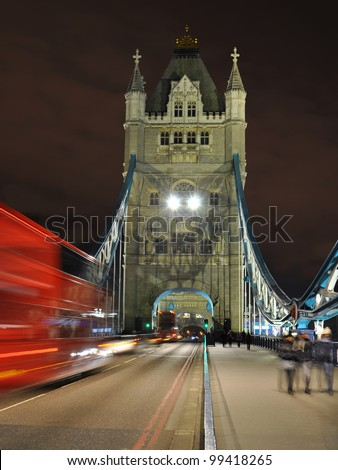 Tower Bridge at night: perspective with red double-decker bus blurred in motion, London, England, United Kingdom. - stock photo