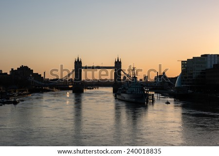Tower Bridge in London silhouetted against a beautiful clear sky and reflected in the waters of the river Thames at sunrise. - stock photo