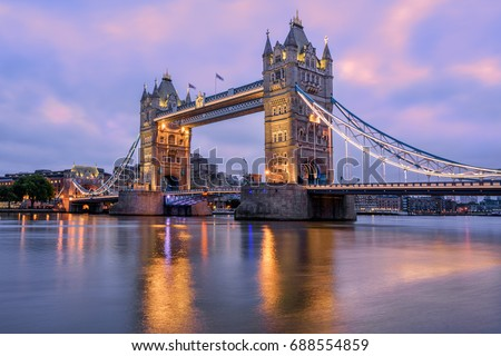 Tower Bridge in London, UK, reflecting in Thames river in dramatic sunrise light