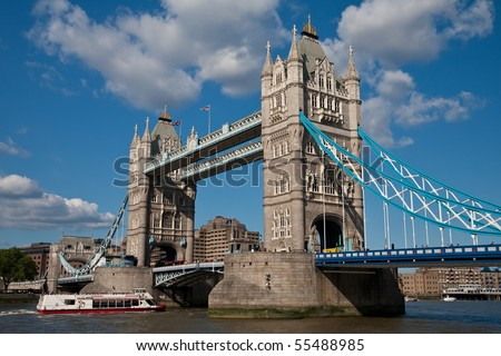 Tower Bridge in London with a boat full of tourists passing through - stock photo