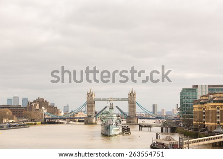 Tower Bridge in London with drawbridge open on a cloudy day. In foreground there is a battleship positioned in the center of the bridge. - stock photo