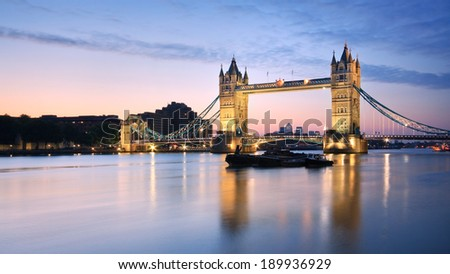 Tower bridge reflecting on Thames in early morning. - stock photo