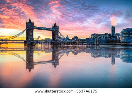Tower Bridge with reflections at sunrise in London.