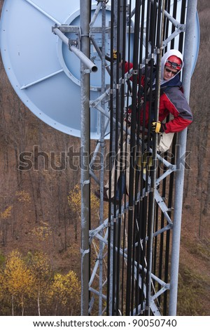 Tower climber inside the guyed tower measuring with the tape the elevation of the dish antenna - stock photo