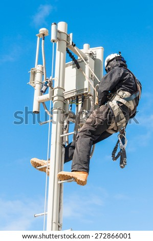 Tower climber on pole tower - stock photo