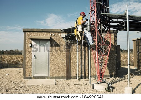 Tower climber starting way up to the top of 300' guyed tower to check the wireless antennas. - stock photo