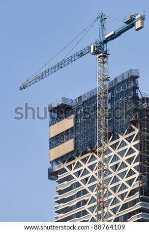 Tower crane and skyscraper - stock photo
