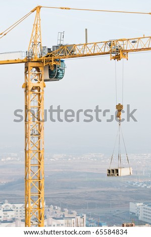 tower crane hoisting concrete blocks load on the top of building under construction - stock photo