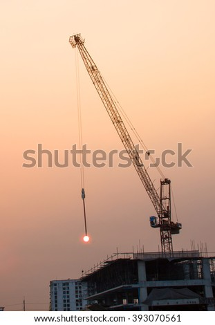Tower crane on a construction site at sunrise, It looks like lifting the sun