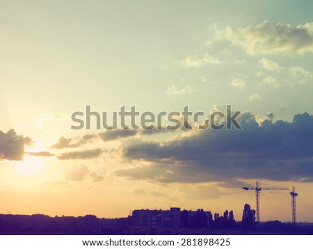 Tower crane on a construction site at sunset. Retro style photo - stock photo