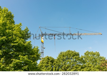 Tower crane on a construction site in the Hamburg district Altona. The construction site is covert with trees - stock photo