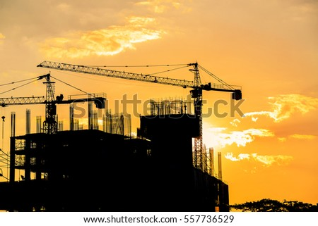 Tower cranes and building silhouettes over sun at sunrise.