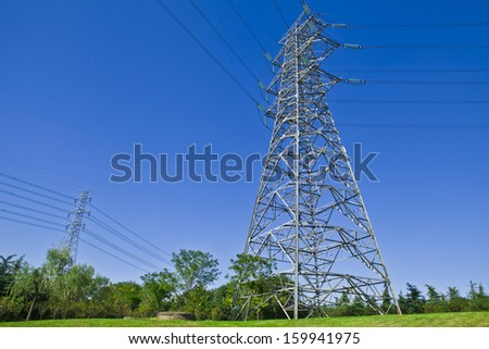 tower for electricity in rural landscape under blue sky  - stock photo
