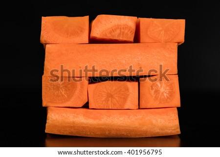 Tower game of carrot sticks (blocks) on dark background. Vegetable sticks children game. Concept - stock photo