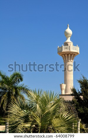 Tower in St. Petersburg rises upward into the morning sun above the trees. The balcony and window are in full view, overlooking the pristine grassy land where it was placed. - stock photo