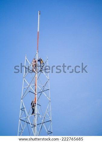 tower makers constructing communication tower, outdoor on blue sky background - stock photo