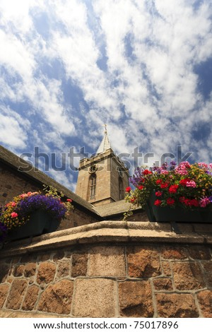 Tower of a church with flowers in the foreground