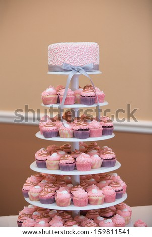 Tower of Cupcakes with a Pink Wedding Cake - stock photo