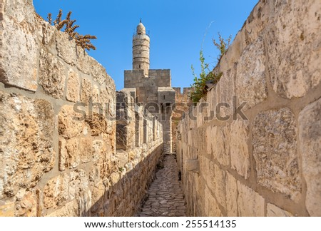 Tower of David and ancient walls under blue sky in Old City of Jerusalem, Israel. - stock photo