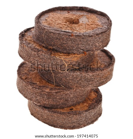Tower of Dried Pressed peat tablet for growing plants  isolated on white background - stock photo