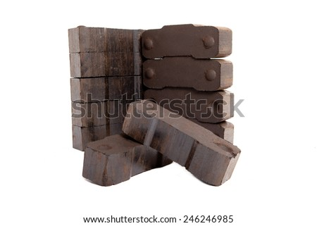 tower of lignite briquettes with two single bricks in front, white background, isolated, copy space,  - stock photo