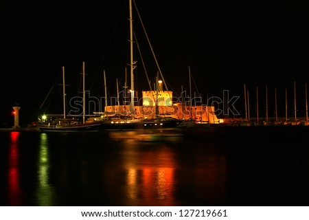 Tower of St. Nicholas in Rhodes (Greece) by night - Bluelight. Motion blur on greek flag and sail masts. Original colors. - stock photo