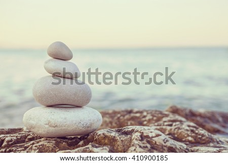 Tower of stones piles on top of a rock on a tranquil deserted beach at evening sunset
