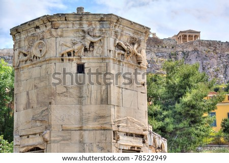 Tower of the Winds (Horologion or Aerides) in Athens, Greece. Compass, sundial, weather vane, water clock. Each face of the frieze has a relief of one of the god winds. Akropolis in the background. - stock photo