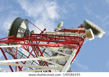 Tower with cell phone antenna system against blue sky - stock photo