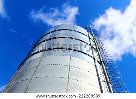 Towering grain silo under blue skies. Storage of grain. - stock photo