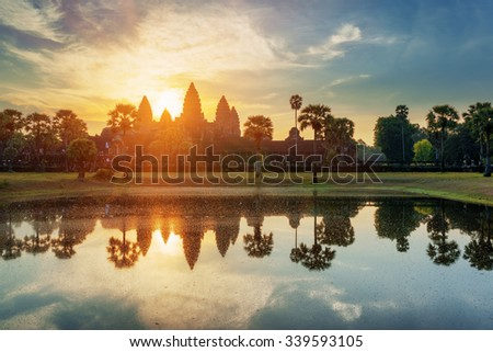 Towers of ancient temple complex Angkor Wat at sunrise. Siem Reap, Cambodia. Temple Mountain and the sun reflected in lake at dawn. Mysterious Angkor Wat is a popular tourist attraction. - stock photo